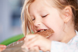 Close Up Of Girl Eating Bar Of Chocolate
